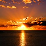 Vibrant sunset over water. Vibrant sunset over the ocean with clouds and sunbeams Stock Image