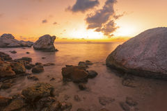 Vibrant sunset at rocky tropical coast Royalty Free Stock Image