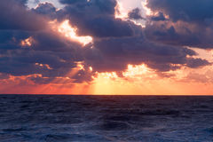 Vibrant sunset sea. Vibrant sunset on the sea with waves on the water surface, clouds on the sky and sun rays. All this makes a specific nature pattern Royalty Free Stock Images