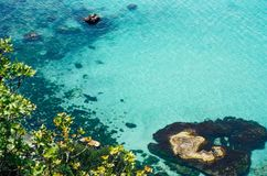 Vibrant top view of blue sea water and rocks royalty free stock photography