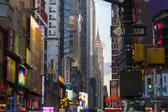 Vibrant view of neon signs, ads and Chrysler Building in background at dusk Royalty Free Stock Photography