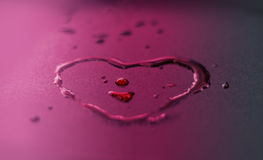 Vibrant water drops heart shape on purple background Royalty Free Stock Photo