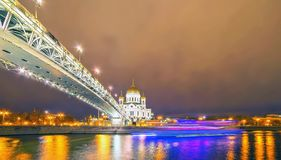 Vibrant wide angle night view of Moscow orthodox church with lamps, golden illuminated cupola,  bridge, river, reflections and. Vibrant wide angle night view of stock photo