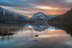 Vibrant Winter Sunrise With Snow On Buttermere Fells In The Lake District. Vibrant orange winter sunrise on a tranquil morning with snowy mountain reflections royalty free stock images