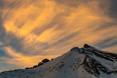 Vibrant yellow sunset over snowy mountains. In the Alps Stock Photography