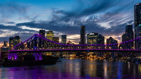 Vibrant zooming night time panorama of Brisbane city with purple lights on Story Bridge stock video