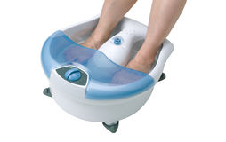 Vibrating feet massager. Woman's feet in a vibrating feet massager Royalty Free Stock Image