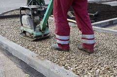 Vibrating machine for repairing asphalt. And worker Royalty Free Stock Photography