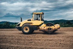 Vibration roller compactor working on highway ground construction site Royalty Free Stock Image