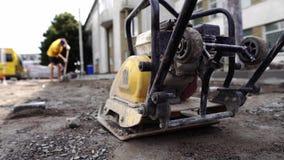 Vibrational brukowego kamienia maszyna dla kona na chodniczek budowy drogi miejscu zostaje na ziemi i kamieniach podczas zdjęcie wideo