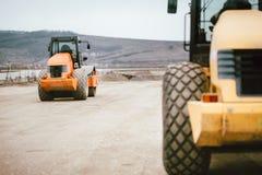 Vibratory jordCompactor under väg- och huvudvägkonstruktion Industriella roadworks med tungt maskineri arkivfoton