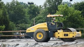 A vibratory roller packer prepares ramp stock footage