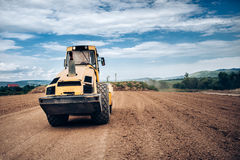 Vibratory Soil Compactor during highway building. Industrial roadworks with heavy-duty machinery Royalty Free Stock Images