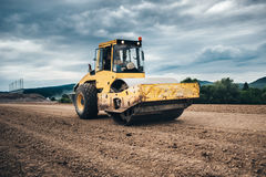 Vibratory soil compactor working on highway construction site Royalty Free Stock Photos
