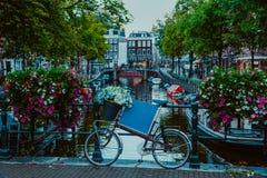 Vibrerande blommor och cykelcykel på en bro av Amsterdam på den tidiga aftonen Skymning på de berömda kanalerna för UNESCOvärldsa arkivfoto