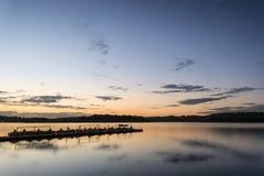 Vibrerande landskap för soluppgång av bryggan på den lugna sjön Royaltyfria Bilder