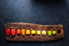 Vibrerande peppar på lantligt bräde arkivbilder