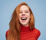 Vibrerande skratta flicka på blå bakgrund arkivbilder