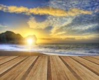 Vibrerande soluppgång över havet med vaggar bunten i förgrund med wo Arkivbild