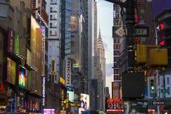Vibrierende Ansicht von Leuchtreklamen, von Anzeigen und von Chrysler-Gebäude im Hintergrund an der Dämmerung Lizenzfreie Stockfotografie