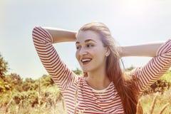 Vibrierende herrliche junge Frau mit Wind im langen Haarlächeln Stockfotografie