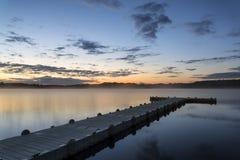 Vibrierende Landschaft des Sonnenaufgangs der Anlegestelle auf ruhigem See Stockfotografie