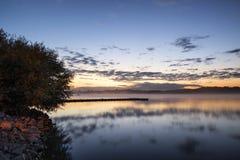 Vibrierende Landschaft des Sonnenaufgangs der Anlegestelle auf ruhigem See Lizenzfreies Stockfoto
