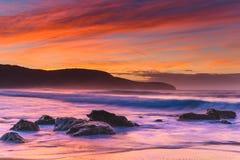 Vibrierender Rocky Sunrise Seascape mit Landspitze und Brandung stockbild