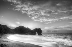 Vibrierender Sonnenaufgang über Ozean mit Felsenstapel im Vordergrund im blac Stockfotos