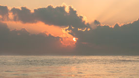 Vibrierender Sonnenaufgang über dem Meer mit Wolken und Sonnenstrahlen Stockbilder