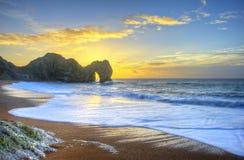 Vibrierender Sonnenaufgang über Ozean mit Felsenstapel im Vordergrund Stockfotos