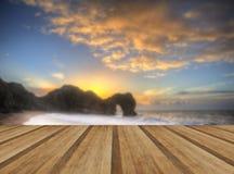 Vibrierender Sonnenaufgang über Ozean mit Felsenstapel im Vordergrund mit wo Stockfotos