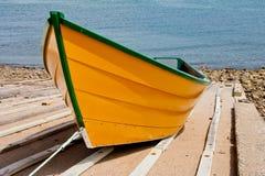Vibrierendes, gelbes Fischenruderboot mit grüner Ordnung Stockbilder
