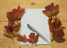 Viburnum berries and leaves with a notebook and pen. Royalty Free Stock Image