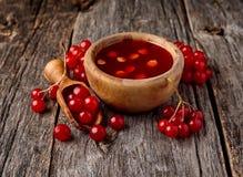 Viburnum oculus. Guelder rose on wooden background.Viburnum berries in wooden scoop.Viburnum souse stock image