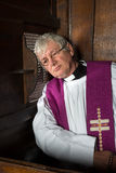 Vicar in confession booth. Vicar listening to the sins of a person in the confession booth Royalty Free Stock Images
