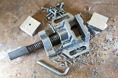 Vice with cuttings. A metal vice with cuttings, screws and tools and pieces of aluminium royalty free stock photo