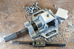 Vice with cuttings. A metal vice with cuttings, screws and tools and pieces of aluminium royalty free stock photography