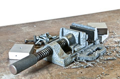 Vice with cuttings, screws and tools. A metal vice with cuttings, screws, tools and pieces of aluminium isolated on white background royalty free stock photos