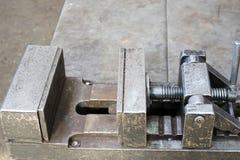 Vice industriel lourd grand en métal avec le mécanisme de vis et les poignées, supports dans l'usine, boutique Fabrication de con photo libre de droits