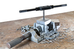 Vice with tap and die. A metal vice with a tap and die isolated on white background stock image