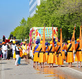 Vicenza, VI, Italy - April 8, 2017: barefooted men with turbans. And scimitars and orange flag at the ceremony of the Sikh religion Royalty Free Stock Image
