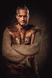 Vichingo arrabbiato in un guerriero tradizionale copre, posando su un fondo scuro immagine stock
