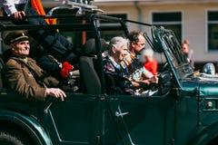 VICHUGA, RUSIA - 9 DE MAYO DE 2016: Veteranos en el coche en la marcha del regimiento inmortal y del desfile el 9 de mayo en la v Fotografía de archivo