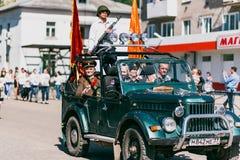 VICHUGA, RUSIA - 9 DE MAYO DE 2016: Veteranos en el coche en la marcha del regimiento inmortal y del desfile el 9 de mayo en la v Foto de archivo