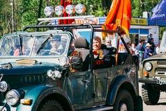 VICHUGA, RUSIA - 9 DE MAYO DE 2016: Veteranos en el coche en la marcha del regimiento inmortal y del desfile el 9 de mayo en la v Imagen de archivo libre de regalías