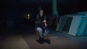 Viciado da menina que senta-se em uma cadeira em uma sala escura que faz uma injeção com drogas video estoque