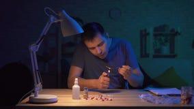 Viciado do homem em uma sala escura em uma tabela que prepara-se para a injeção filme