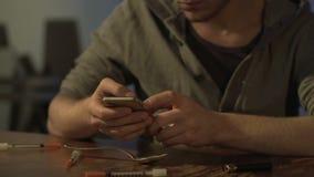 Viciado em drogas nervoso que texting no smartphone ao negociante, procurando a dose da heroína vídeos de arquivo