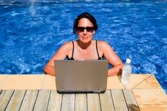 Viciado em trabalho executivo fêmea que trabalha no laptop no swimmi Imagens de Stock Royalty Free